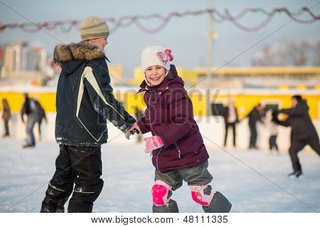 Brother and sister having fun skating on the rink