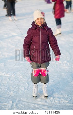 Smiling little girl in knee pads skating at the rink in winter