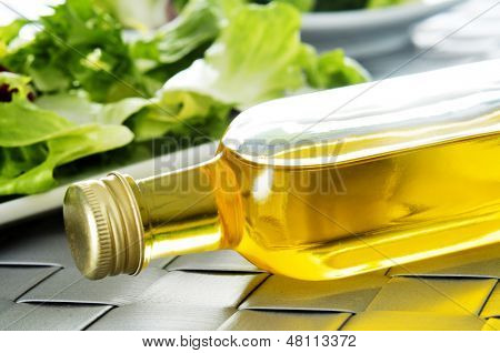 closeup of bottle of spanish olive oil on a set table, with a plate with lettuce in the background