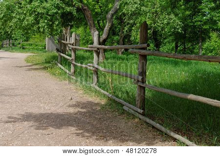 Rural path enclosed with lath fence at summer