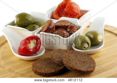 A Plate Of Bread, Tapas; Olives, Tomatoes, Pepper And Marinated Sausages On White