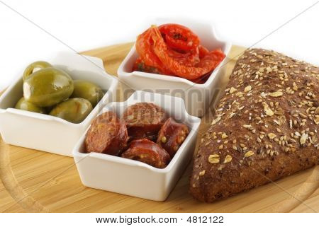 A Plate Of Bread, Tapas, Olives, Tomatoes And Marinated Sausages On White