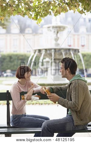 Side view of a happy young couple eating baguette on park bench