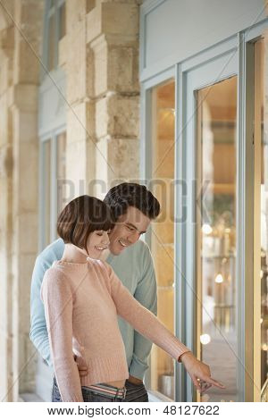 Side view of a couple looking in shop window