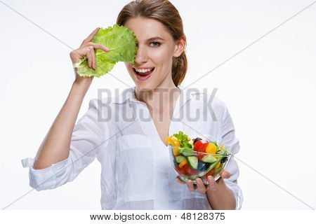 Young beautiful woman with vegetable salad bowl in one hand and cabbage leaf in other hand isolated