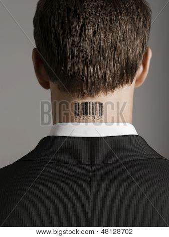 Closeup Rückansicht eines jungen Kaufmanns mit Barcode-Tattoo am Hals vor grauem Hintergrund