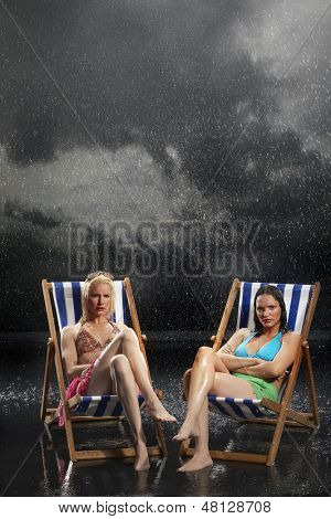 Full length of two young women sitting in sunloungers during downpour