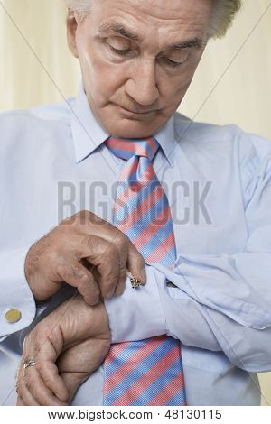 Closeup of a senior businessman fixing cuff links
