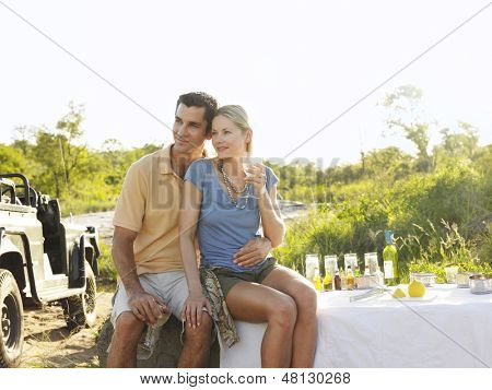 Young couple at picnic during safari with jeep in the background