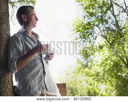 Side view of a man leaning on tree and drinking tea