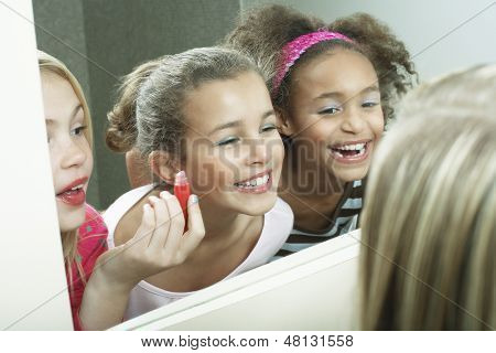 Closeup of three happy girls putting on makeup and lipgloss