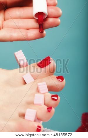Foot Pedicure Applying Red Toenails On Blue