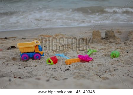 Children's plastic toy on the beach by the sea.