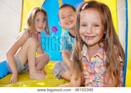Three kids inside an outdoor camping tent