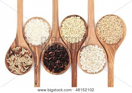 Rice varieties in olive wood spoons over white background. Wild, white, american, sweet, risotto and brown left to right.