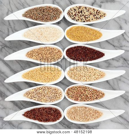 Healthy grain food selection in white china porcelain dishes over marble background.