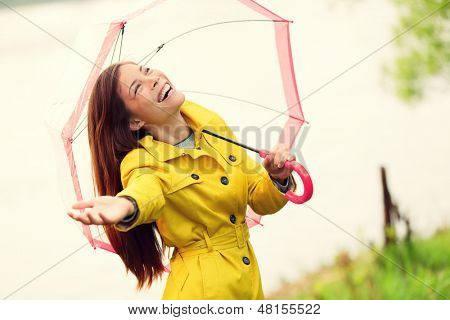 Fall woman happy after rain walking with umbrella. Female model looking up at clearing sky joyful on rainy Autumn day wearing yellow raincoat outside in nature forest by lake. Mixed race Asian girl.