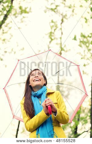 Asian woman in Autumn happy with umbrella in rain. Female model looking up at clearing sky joyful on rainy fall day wearing yellow raincoat outside in nature forest by lake. Mixed race Asian girl.