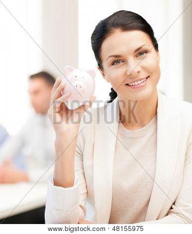 business and money saving concept - woman with piggy bank