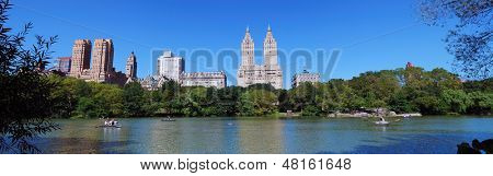 New York City Central Park panorama with Manhattan skyline skyscrapers and blue sky with boat in lake.