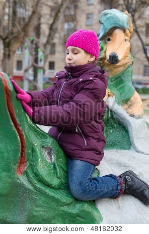 MOSCOW -  NOV 10: Anya 7 years old playing in playground with sculptures made by Krylovs fables on Nov 10, 2012 in Moscow, Russia. Ivan Krylov was born February 13, 1769 and died November 21, 1844.