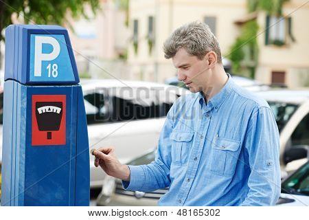 junger Mann zu Parkuhr zu zahlen