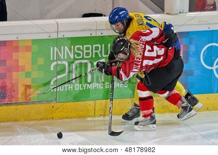 INNSBRUCK, AUSTRIA - JANUARY 17 Julia Willenshofer (Austria) and Sabina Kueller (Sweden) fight for the puck in the ladies' ice hockey tournament on January 17, 2012 in Innsbruck, Austria.