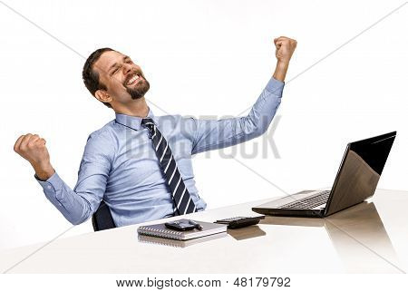 young modern businessman excited with his success while working with his laptop computer