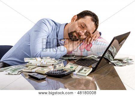 Worried businessman sleeping at office desk being overloaded with work and accounting money