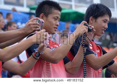 DONETSK, UKRAINE - JULY 14: Japanese fans make photos after the final round of medley relay during 8th IAAF World Youth Championships in Donetsk, Ukraine on July 14, 2013