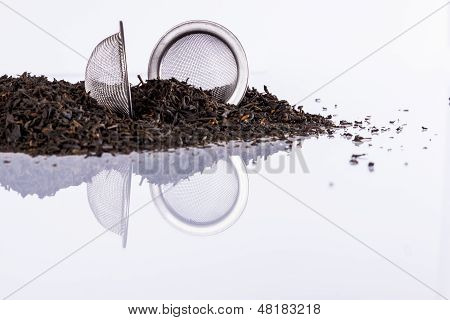 Black Tea And Tea Strainer On White Background.