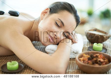 Portrait of young female enjoying spa procedure in beauty salon