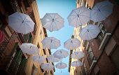 Street decorated with open hanging umbrellas to protect from the sun