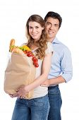 Portrait Of Happy Young Couple With Grocery Bag Isolated On White Background
