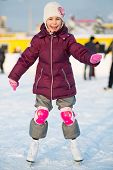 Smiling little girl in knee pads skating at the rink