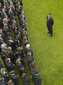Elevated view of businessman facing large group of business people