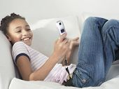 pic of tweeny  - Side view of a cheerful young girl using cellphone - JPG