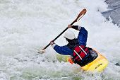 stock photo of rough-water  - an active female kayaker rolling and surfing in rough water - JPG