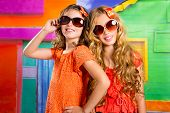 children friends girls with fashion sunglasses in vacation at tropical colorful house