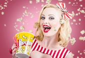 stock photo of comedy  - Retro photograph of a beautiful vintage girl with surprise expression watching premier film at movie theater amongst raining popcorn - JPG