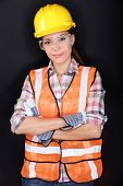 Construction worker with safety vest, glasses and hardhat portrait on black background. Portrait of
