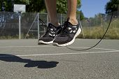 foto of legs air  - Male using a jump rope on a basketball court - JPG
