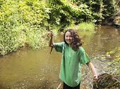 picture of brook trout  - Photo of young girl holding up small trout while fishing on a small stream - JPG