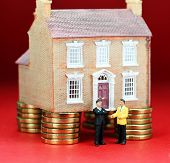 stock photo of stubborn  - A real estate agent and a prospective buyer in front of a house on gold coin stilts - JPG