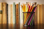 stock photo of sketch book  - Wire desk tidy full of coloured pencils standing on a wooden table in front of a bookshelf full of books with shallow dof and copyspace - JPG