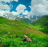 Happy female hiker lying on the meadow, icy peaks on background