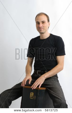Man Sitting On Suitcase