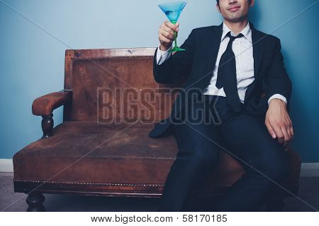 Happy Businessman Toasting While Sitting On Old Couch