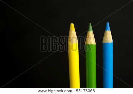 Yellow, Green And Blue Coloured Pencil Crayons On A Black Background