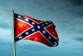 stock photo of rebel flag  - Confederate flag waving in the evening on the sky - JPG